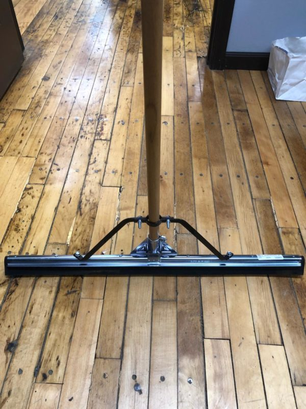 Photo of Squeegee with metal top and rubber bottom resting on wood floor.