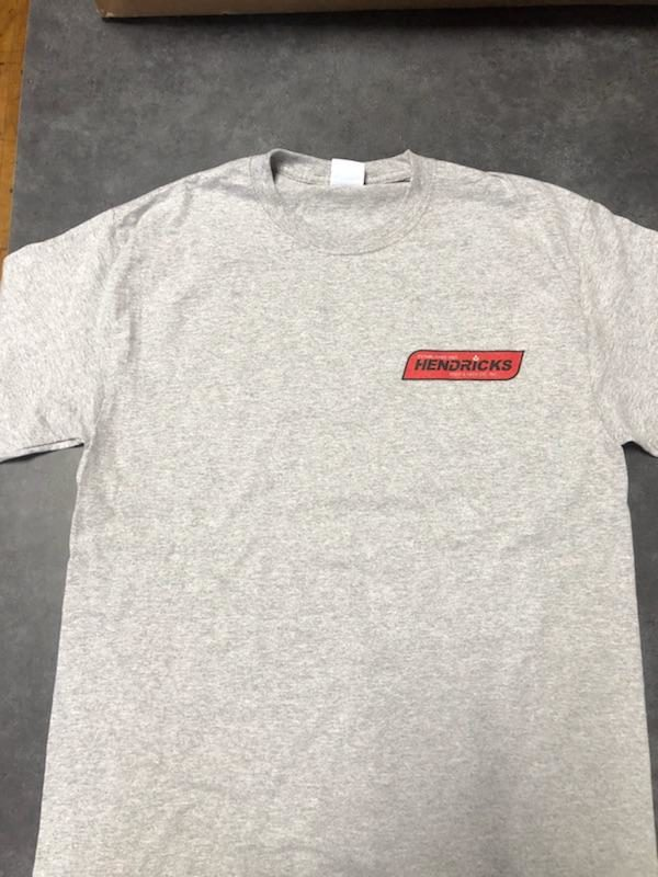Photo of gray Hendricks T-shirt with red Hendricks logo in corner and black outline.
